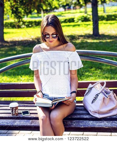 Young beautiful brunette student in glasses sits on a bench in the park summer day, reading a book, coffee, tea, mobile phone bag, tanned relaxing after lessons at the institute in the fresh air.