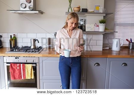 Woman Standing In Kitchen Sending Text Message On Phone