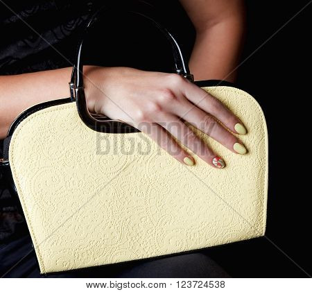Close-up a pretty woman bag with matching nails