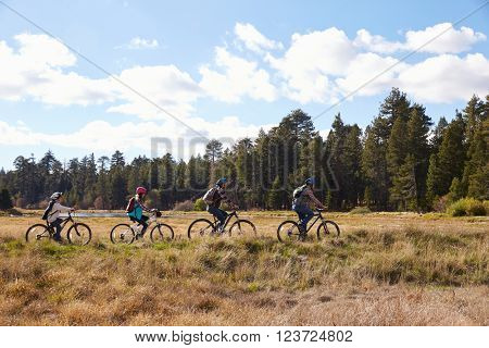 Family mountain biking in countryside, California