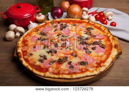 pizza with ham, cheese, mushrooms and  pizza ingredients on the table