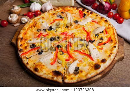 pizza with chiken, cheese, vegetables and  pizza ingredients on the table