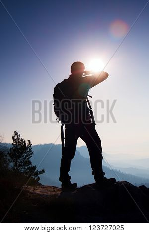 Tourist With Sporty Backpack Stand On Rocky View Point And Watching Into Misty Valley Bellow. Sunny