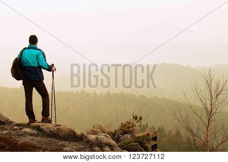 Tourist With Backpack And Poles In Hand  Stand On Rocky View Point And Watching Into Misty Valley Be