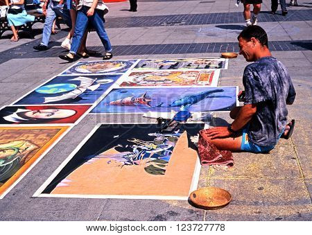 NOTTINGHAM, UK- MAY 16, 1992 - Pavement artist sitting on the floor in the city centre Nottingham Nottinghamshire England UK Western Europe, May 16, 1992.