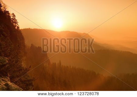 Red misty daybreak. Foggy autumn morning in a beautiful hills. Peaks of hills are sticking out from foggy background, the fog is red and orange due to Sun rays. ** Note: Soft Focus at 100%, best at smaller sizes