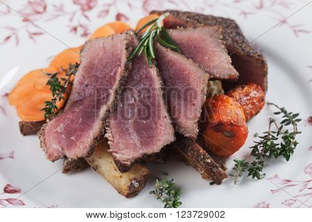 Slices of medium rare beef pepper steak with carrot, thyme and rosemary