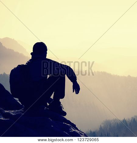 Tired Hiker With Sporty Backpack Sit On Rocky Peak And Watching Into Deep Misty Valley Bellow. Sunny
