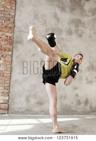 Handsome kickboxer on a grey background