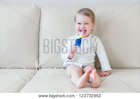 Smiling baby girl making inhalation and inspiration