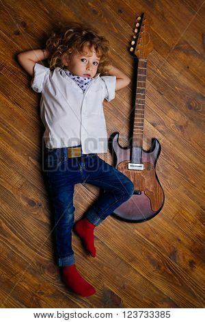 Little Boy Lying And Hugging Guitar On Wooden Floor