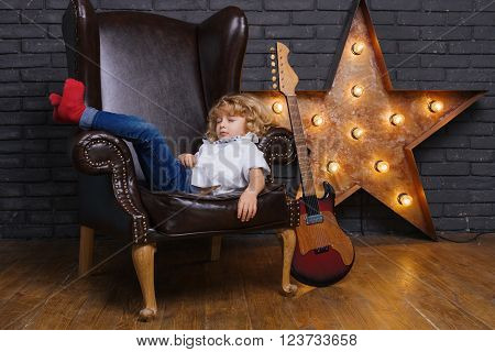 Little Boy Sleeping On Brown Leather Chair Near Iron Star On Brick Wall Background