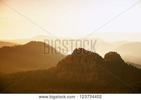 Red misty landscape panorama in mountains. Fantastic dreamy sunrise on rocky mountains with view down to foggy misty valley below
