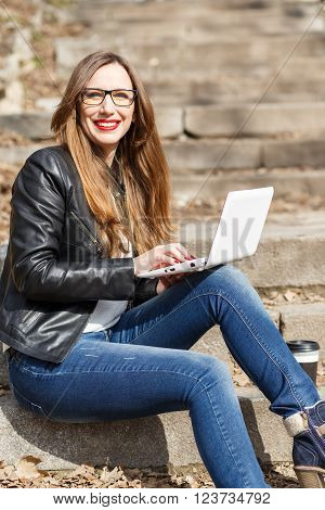 Young Woman In Leather Jacket Using Laptop