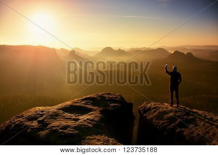 Man takes photos with smart phone on peak of rock empire. Dreamy fogy landscape spring orange pink misty sunrise in a beautiful valley of rocky mountains.