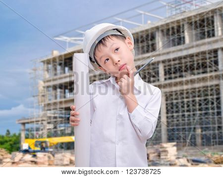 Asian boy with helmet thinking in front of construction site