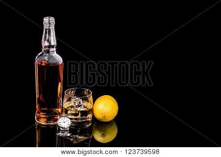 Bottle and glass whiskey with ice and wrist watch on black background