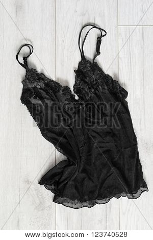 Black lacy lingerie top on wooden white background closeup