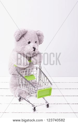 Little shopping cart and a teddy bear. Conceptual image for sale of toys or children's fantasies