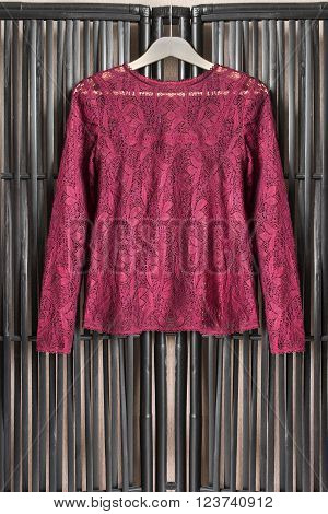 Maroon lacy blouse on clothes rack hanging on wooden screen