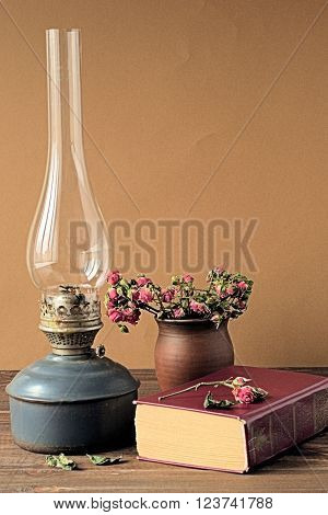 Old kerosene lamp, a book and a pot with dried flowers on a brown background.