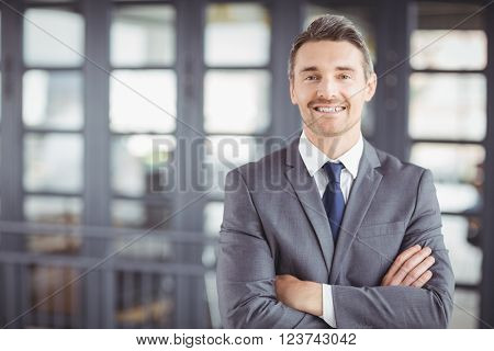 Portrait of smiling businessman with arms crossed standing in office