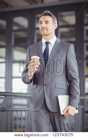 Low angle view of businessman walking while holding disposable cup and digital tablet