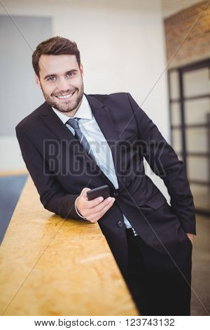 Portrait of businessman using cellphone while leaning on counter at office