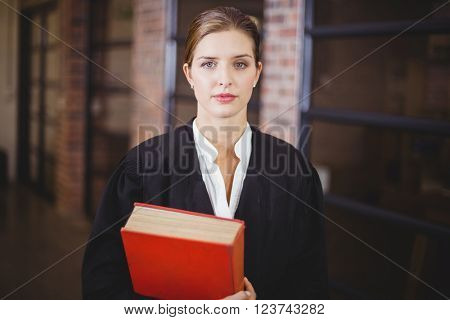 Portrait of confident female lawyer with book standing in office