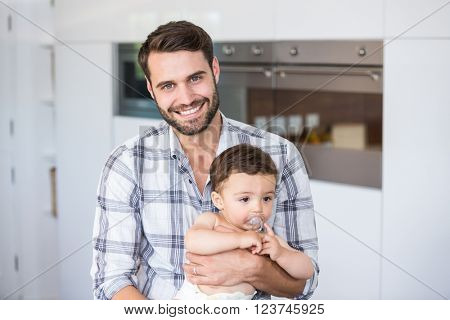 Portrait of man smiling while carrying son at home