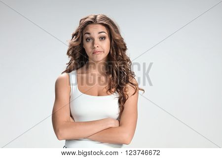 The young happy thoughtful  woman on gray background. concept of regret