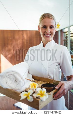 Smiling masseuse holding a tray at the spa