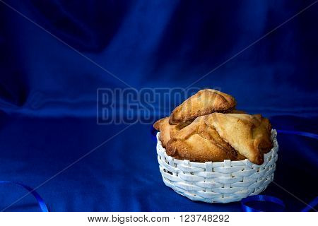 Hamantaschen or Haman's ears - triangular cookies for Jewish holiday of Purim on dark blue silk background