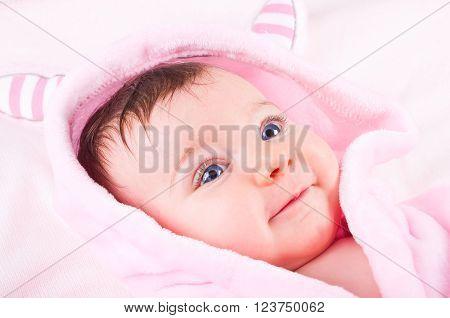Beautiful funny baby girl in pink bathrobe.