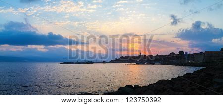 Beautiful sunrise on the coast of the Black Sea. Old Nessebar in Bulgaria. The rays of the rising sun in the background of the sky with cumulus clouds. Dawn at the seaside. Silhouettes of houses and boats. Panoramic shot.