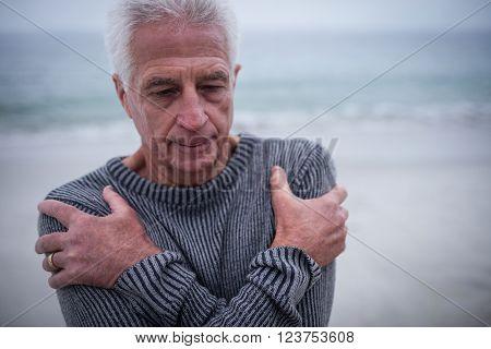 Senior man in sweater feeling cold on beach