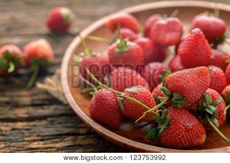 Rotten strawberries in wooden plate on wooden table on blurred background
