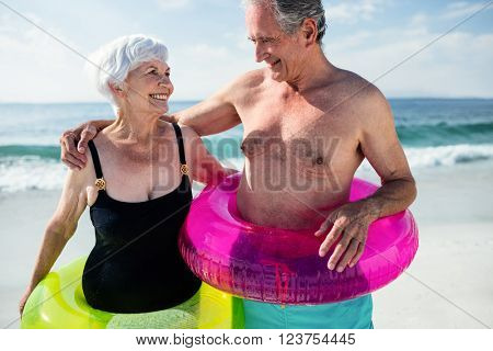 Senior couple in inflatable ring standing on beach on a sunny day