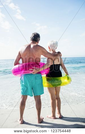 Rear view of senior couple in inflatable ring standing on beach