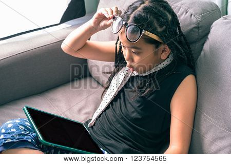 Cute little girl,wearing glasses,dreadlocks hair style ,playing with computer at home laying on sofa
