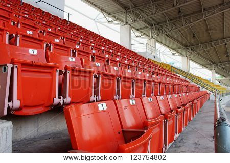 Red seats on the grandstand in the stadium.