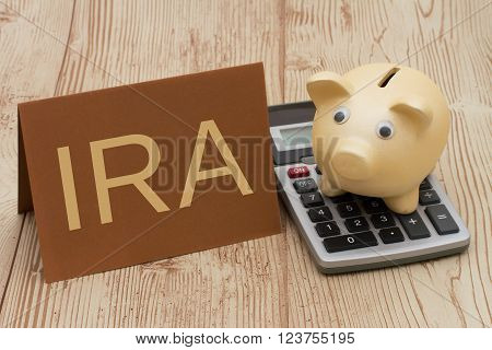 Having a IRA plan, A golden piggy bank, card and calculator on wood background with text IRA
