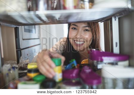 Portrait of young woman picking a bottle from storage cabinet in kitchen