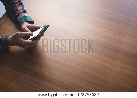 Woman sitting at table and typing a text message on her mobile phone