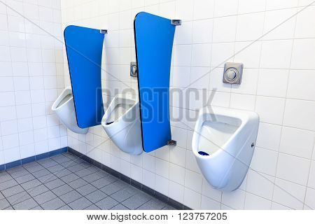 Boy's urinals on white wall with blue partitions in high school
