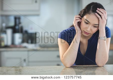 Worried young woman sitting in kitchen at home