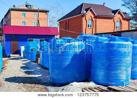 blue plastic water tank in the open air. Production of water tanks