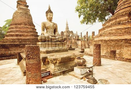 SUKHOTHAI, THAILAND - FEB 16: Asian religious art landmark - Brick temple Wat Maha That with Buddha statue at Sukhothai historical park on February 16, 2015. Sukhothai historical park is a UNESCO World Heritage Site.