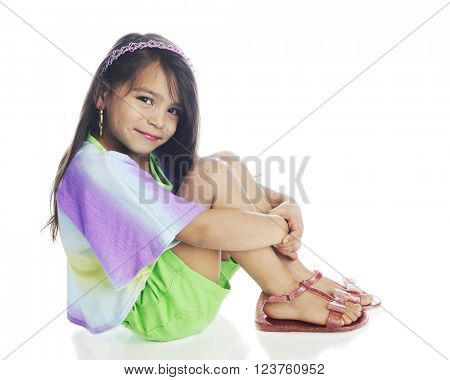 A beautiful young girl happily looking at the viewer while sitting pretty in her shorts, multicolored shirt and sandals.  On a white background.