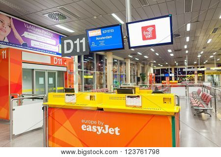 MALPENSA, ITALY - JULY 07, 2015: Easyjet counter at boarding gate Terminal 2 of Malpensa Airport - largest international airport in Northern Italy and  28th busiest in Europe in terms of passengers.